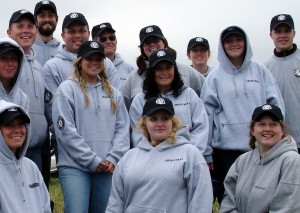 A smiling group of Americorps participants in gray hoodies and PMSC logo caps posing for a group photo.