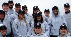 A group of smiling PMSC volunteers, most in their twenties or early thirties, wearing logo hoodies and ballcaps.