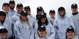 A smiling group of PMSC volunteers in logo hoodies and ballcaps.